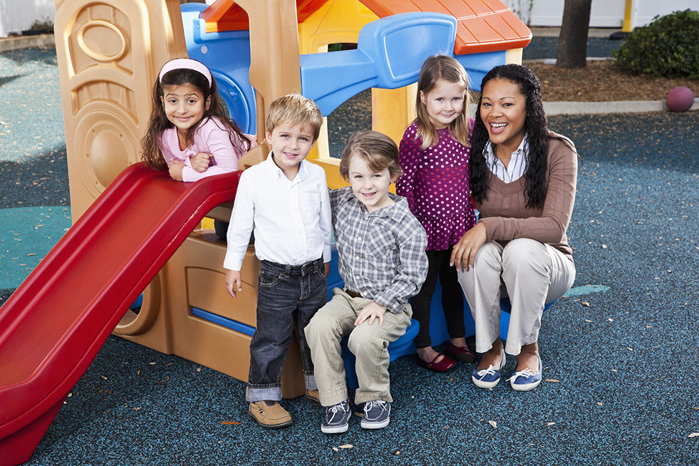 Teacher (20s) with preschoolers on playground (3-4 years).