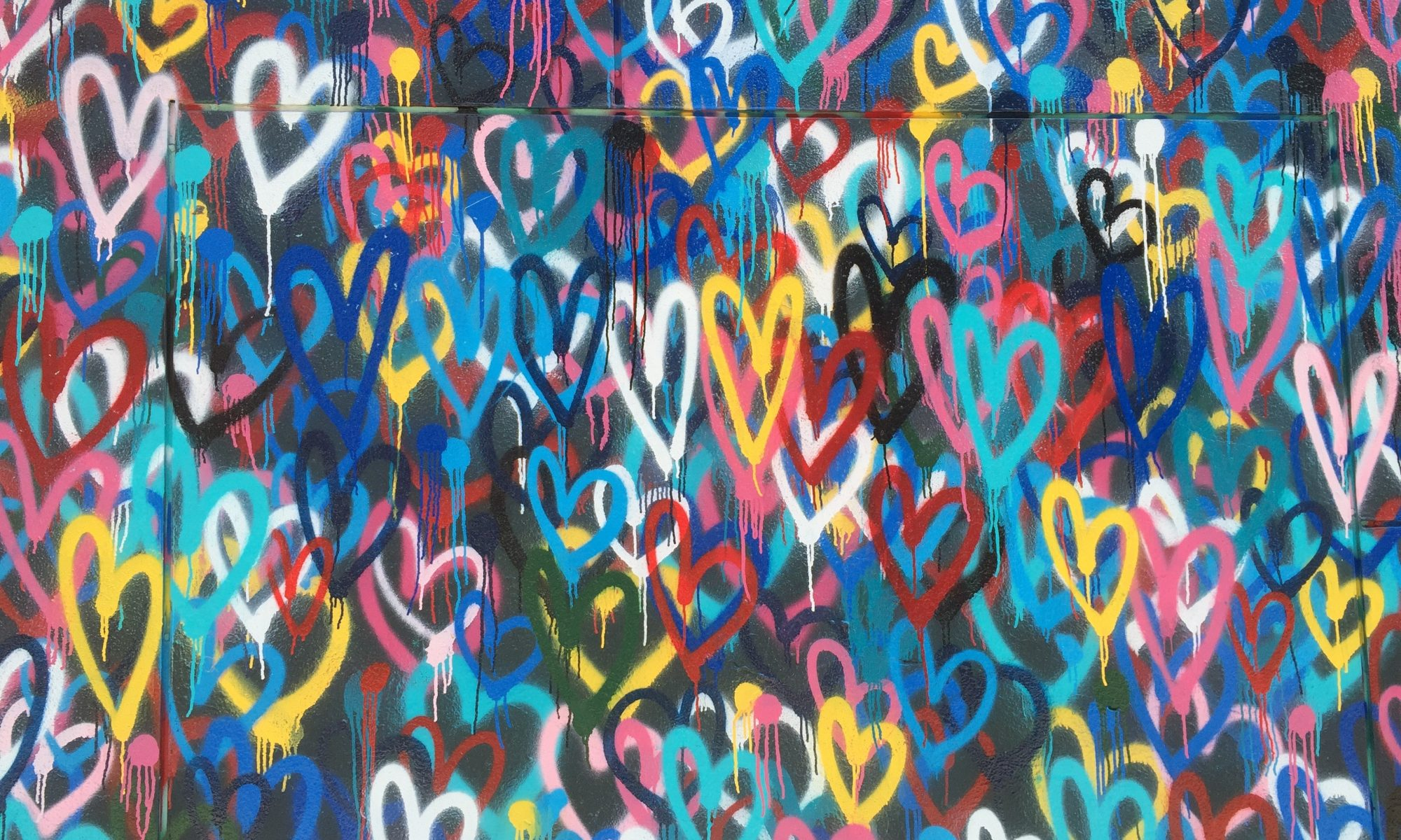Wall of colour spray-painted hearts_Photo by Renee Fisher on Unsplash