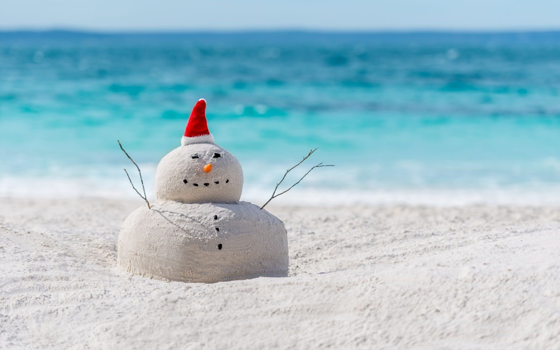 Snowman made from sand in a santa hat on the beach